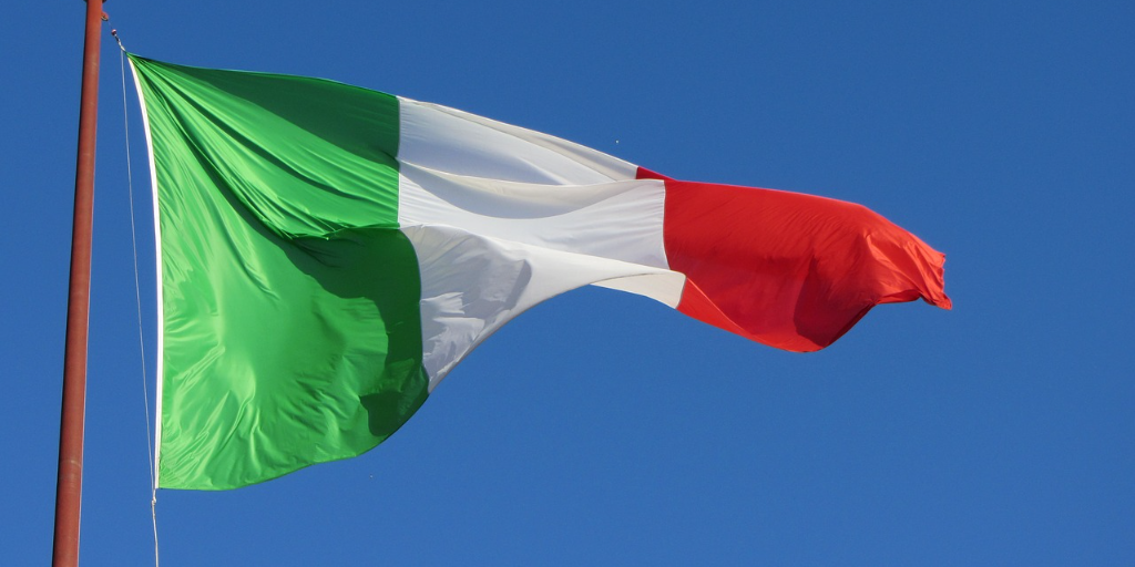 Green, white, and red Italian tricolor flag waving against a blue sky